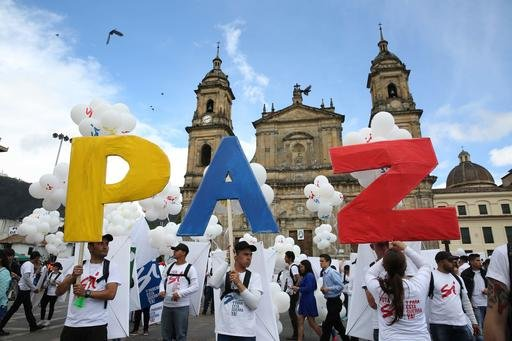 "People hold up letters that form the word ""Peace"" in Spanish during a gathering at Bolivar square in Bogota, Colombia, Monday, Sept. 26, 2016. Colombia's government and the Revolutionary Armed Forces of Colombia signed a peace agreement to end over 50 yea"