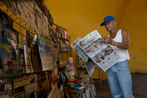 "Saul Lambis reads a newspaper carrying the headline in Spanish ""Agreement Signing"" in Cartagena, Colombia, Tuesday, Sept. 27, 2016, the day after the government signed a peace agreement with the Revolutionary Armed Forces of Colombia, FARC, to end over 50"
