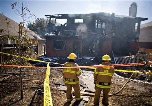 Two firemen are seen at the home belonging to Joseph Stack, after Stack apparently set it on fire according to two law enforcement officials, Thursday morning on Feb. 18, 2010 in Austin, Texas.