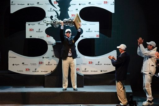 Marcus Young, commodore of the Golden Gate yacht club of San Francisco raises the America's Cup trophy as BMW Oracle Racing owner Larry Ellison, right, applauds during the podium ceremony in Valencia, Spain, on Sunday, Feb. 14, 2010.