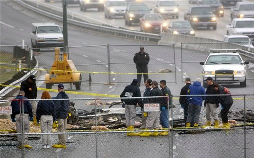 Members of the FBI, Austin Police and unknown other agencies huddle around aircraft and building debris on the service road by a building that a plane was flown into, Friday, Feb. 19, 2010, in Austin, Texas.