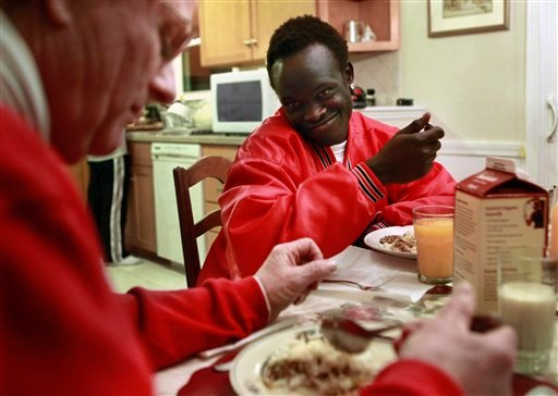 Sudanese war refugee Madhel Majok, 17, left, now a high school student in Holliston, Mass., chats with foster parent Paul Boulanger, left, over dinner at their home in Holliston.