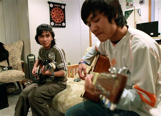 Refugees from Myanmar Lian Sian Kim, 18, right, and his brother Lian Sian Sang, 16, left, play guitars together at their foster home in Leicester, Mass.