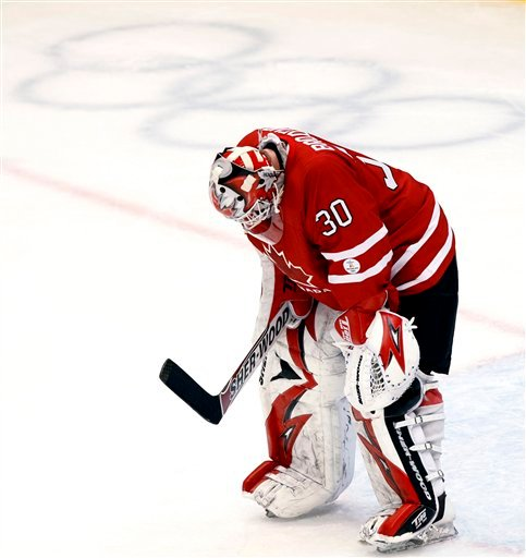 Canada's goaltender Martin Brodeur reacts after letting in the fourth goal by team U.S.A. during third period men's ice hockey action Sunday, Feb. 21, 2010. (AP Photo/The Canadian Press, Ryan Remiorz)