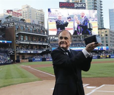 Dick Enberg, a San Diego Padres broadcaster, holds up a microphone trophy presented to him for his retirement, prior to the Padres' final baseball home game of the season, against the Los Angeles Dodgers on Thursday, Sept. 29, 2016, in San Diego. (AP Phot