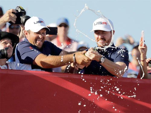 United States? Patrick Reed and United States? Jimmy Walker sprays fans with Champagne after the United States team won the Ryder Cup golf tournament Sunday, Oct. 2, 2016, at Hazeltine National Golf Club in Chaska, Minn.