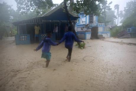 Residents wade through flood waters in Leogane, Haiti, Tuesday, Oct. 4, 2016. Matthew slammed into Haiti's southwestern tip with howling, 145 mph winds Tuesday, tearing off roofs in the poor and largely rural area, uprooting trees and leaving rivers bloat