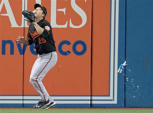 Baltimore Orioles' Hyun Soo Kim gets under a fly ball as a can falls past him during the seventh inning of an American League wild-card baseball game against the Toronto Blue Jays in Toronto.