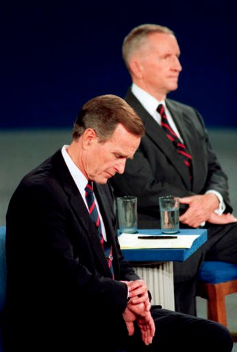 (AP Photo/Ron Edmonds, File). FILE - In this Oct. 15, 1992, file photo President George H.W. Bush looks at his watch during the 1992 presidential campaign debate with other candidates, Independent Ross Perot, top, and Democrat Bill Clinton, at the Univ...