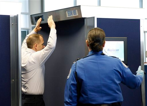Transportation Security Administration employee John Carter demonstrates the stance in an advanced image technology unit as TSA supervisory officer Diana Hernandez operates the machine at Boston Logan International Airport, Friday, March 5, 2010.