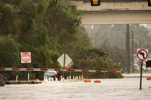 (AP Photo/Stephen B. Morton). An unidentified woman is rescued from her vehicle which is floating in waist-deep water on flooded President Street after Hurricane Matthew caused flooding along the east coast of Georgia, Saturday, Oct. 8, 2016, in Savann...