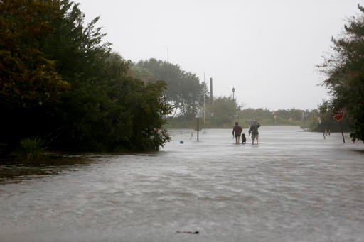 (AP Photo/Mic Smith). People walk down Station 30 with their dog as Hurricane Matthew hits Sullivan's Island, S.C., Saturday, October 8, 2016. Matthew is continuing its march along the Atlantic coast, lashing two of the South's most historic cities a...