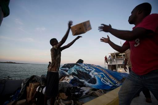 "(AP Photo/Dieu Nalio Chery). People unload food and water boated in from the ""Mission of Hope"" charity after Hurricane Matthew swept through Jeremie, Haiti, Saturday, Oct. 8, 2016. Jeremie appears to be the epicenter of the country's growing humanitari..."