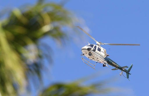 (Omar Ornelas/The Desert Sun via AP). A Sheriff Department helicopter assists in a manhunt after two Palm Springs, Calif., police officers trying to resolve a family dispute were shot to death Saturday, Oct. 8, 2016, when a man they had been speaking ...
