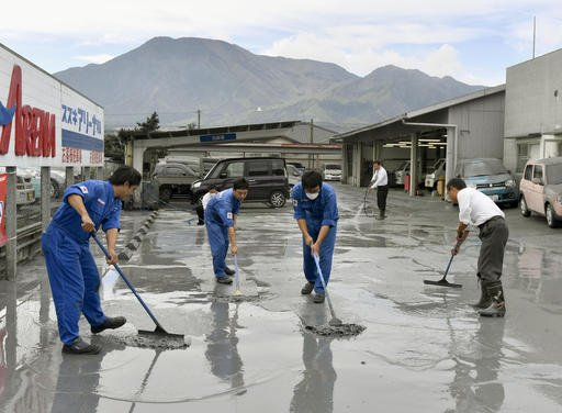 (Hiroko Harima/Kyodo News via AP). Auto dealership workers clean volcanic ash from the eruption of Mount Aso, back, in Aso city, Kumamoto prefecture, on the southern Japanese main island of Kyushu, Saturday, Oct. 8, 2016. Mount Aso has sent huge plume...