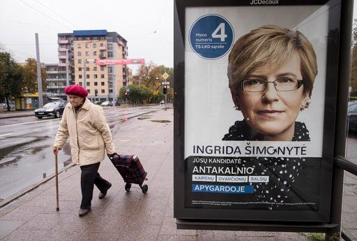 (AP Photo/Mindaugas Kulbis). A woman walks by an election poster showing Homeland Union member Ingrida Simonyte in Vilnius, Lithuania, Friday, Oct. 7, 2016. Lithuanians elect a new parliament on Sunday, Oct. 9, 2016.