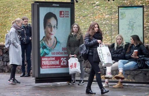 (AP Photo/Mindaugas Kulbis). Local residents in Vilnius wait at the bus stop with a picture of Social Democratic Party member Marija Ausrine Povilioniene in Vilnius, Lithuania, Friday, Oct. 7, 2016. Lithuanians elect a new parliament on Sunday, Oct. 9,...