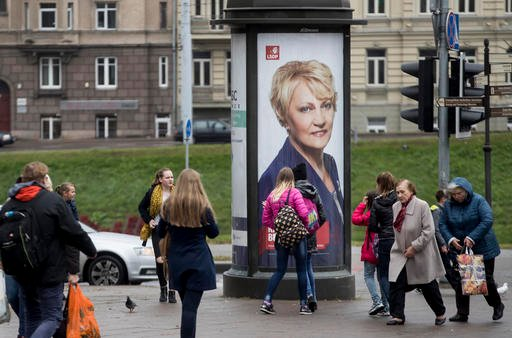 (AP Photo/Mindaugas Kulbis). A local residents walks past an election poster showing Social Democratic Party member Rasa Budbergyte in Vilnius, Lithuania, Friday, Oct. 7, 2016. Lithuanians elect a new parliament on Sunday, Oct. 9, 2016.