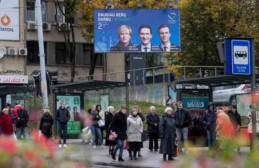(AP Photo/Mindaugas Kulbis). A local residents wait at the bus stop, near election poster showing Homeland Union leader Gabrielius Landsbergis, right, and Union members Ingrida Simonyte, left, and Dainius Kreivys in Vilnius, Lithuania, Friday, Oct. 7, ...