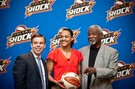 Former sprinter Marion Jones , center, smiles while flanked by Tulsa Shock president Steve Swetoha, , left, and coach Nolan Richardson during a news conference announcing her signing with WNBA basketball Tulsa Shock.