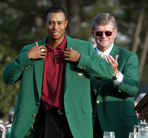 """In this April 14, 2002, file photo, Tiger Woods, left, adjusts the 2002 Masters Green Jacket he received from Augusta National Golf Club chairman William W.""""Hootie"""" Johnson, as Johnson applauds at the Augusta National Golf Club in Augusta, Ga."""