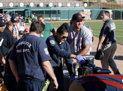 Scottsdale Scorpions outfielder Tim Tebow, center, comforts a fan, on ground, who was suffering a seizure, following Tebow's debut against the Glendale Desert Dogs in a baseball game.
