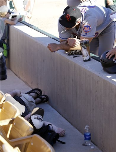 Scottsdale Scorpions outfielder Tim Tebow stands near a fan who, the Phoenix Fire Department said, was having a seizure.