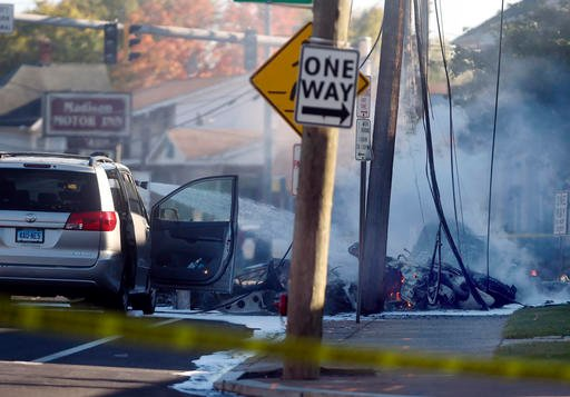 (Jim Michaud/Journal Inquirer via AP). Smoke pours from the smoldering remains of a small plane that crashed on Main Street in East Hartford Conn., Tuesday, Oct. 11, 2016. Authorities said at least one person is dead and another is injured after a smal...