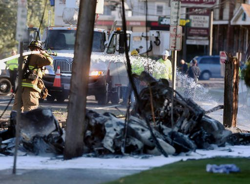 (Jim Michaud/Journal Inquirer via AP). Firefighters use foam to extinguish the fire of a demolished aircraft after the plane crashed on Main Street in East Hartford Conn., Tuesday, Oct. 11, 2016. Authorities said at least one person is dead and another...