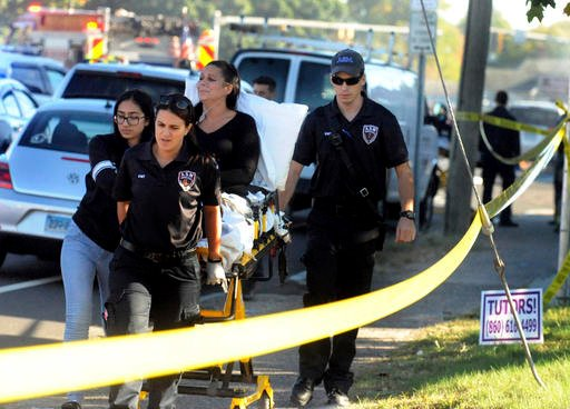 (Jim Michaud/Journal Inquirer via AP). A woman who was on the ground is taken away after a plane crash on Main Street in East Hartford Conn., Tuesday, Oct. 11, 2016. Authorities said one person is dead and another is injured after a small airplane cras...
