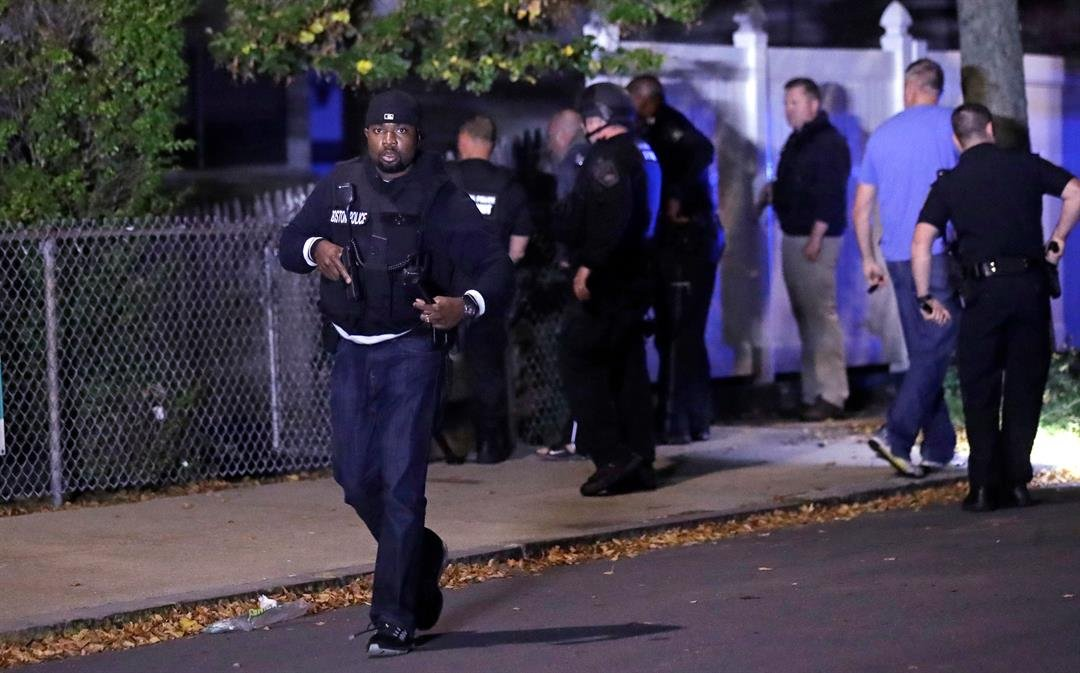 Police search for a suspect after a shooting in the East Boston neighborhood of Boston, Wednesday, Oct. 12, 2016. Police say two officers were shot late Wednesday night. Their conditions were not immediately available. It's unclear what led to the shootin