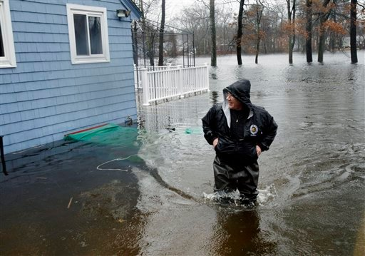 Peter Auchterlonie wears waders to walk around his flooded home along the Shawsheen River in Billerica, Mass. Monday, March 15, 2010. (AP Photo/Elise Amendola).