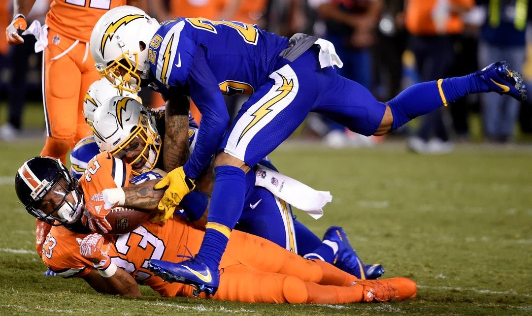 Denver Broncos running back Devontae Booker, bottom, is brought down by San Diego Chargers cornerback Craig Mager, above, and free safety Dwight Lowery during the second half of an NFL football game Thursday, Oct. 13, 2016, in San Diego. (AP Photo/Denis P