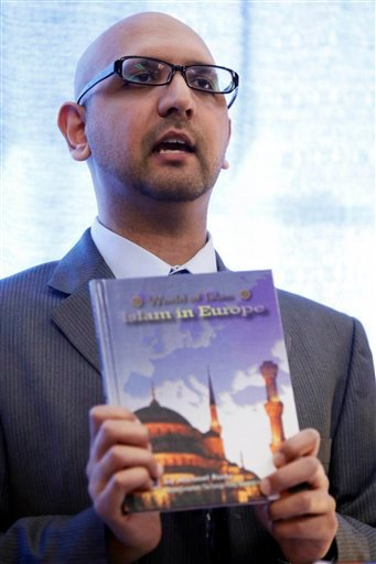 """Moein Khawaja, with the Council on American-Islamic Relations, displays a """"World of Islam"""" book by Mason Crest Publishing during a news conference in Philadelphia."""