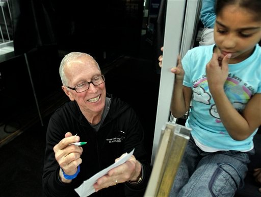 San Diego State head coach Steve Fisher, left, signs an autograph for Lauren Geremia, 8, of Providence, R.I., after NCAA college basketball practice in Providence, Wednesday, March 17, 2010.