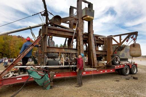 "(AP Photo/Jim Cole). In this Saturday, Oct. 15, 2016 photo, Chuck Willard, of Hancock, N.H., works the controls on his pumpkin thrower ""Tired Iron""in Loudon, N.H. Months of welding discarded iron, his contraption catapults a 9-pound pumpkin almost half..."