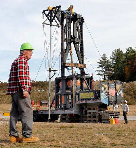 """(AP Photo/Jim Cole). In this Saturday, Oct. 15, 2016 photo, dentist Steve Seigars from Greenfield, N.H. gets ready to catapult a pumpkin from his contraption """"Yankee Siege II"""" during a pumping launching contest at New Hampshire Motor Speeday in Loudon,..."""