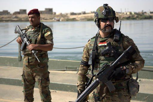 (AP Photo/Adam Schreck, File). FILE -- In this Saturday, Oct. 15, 2016 file photo, Iraqi soldiers secure a temporary pontoon bridge near Qayara Air Base, northern Iraq. Iraqi forces appear poised to launch their most complex anti-IS operation to date: