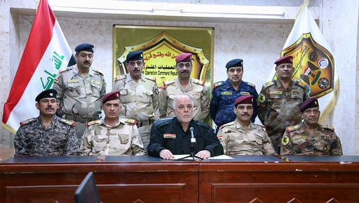 (Iraq Prime Minister's office via AP). This photo released on his official Facebook page shows Iraqi Prime Minister Haider al-Abadi, center, surrounded by top military and police officers as he announces the start of the operation to liberate the north...