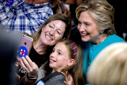 (AP Photo/Andrew Harnik). Democratic presidential candidate Hillary Clinton takes a photograph with supporters at a campaign office in Seattle, Friday, Oct. 14, 2016.