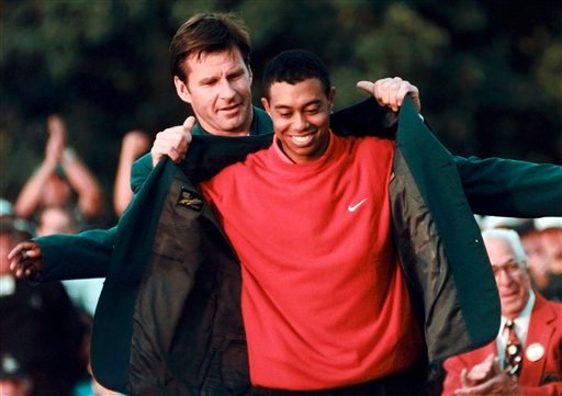 In this April 13, 1997, file photo, Masters champion Tiger Woods receives his green jacket from the previous year's winner Nick Faldo, rear, at the Augusta National Golf Club in Augusta, Ga.