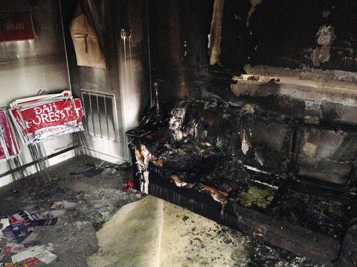 (AP Photo/Jonathan Drew). A burned couch is shown next to warped campaign signs at the Orange County Republican Headquarters in Hillsborough, NC on Sunday, Oct. 16 2016. Someone threw flammable liquid inside a bottle through a window overnight and some...