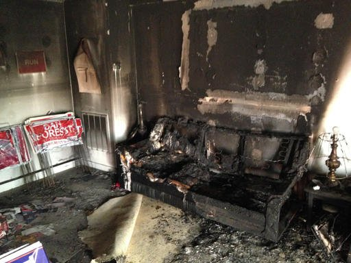 (AP Photo/Jonathan Drew). A burnt couch is shown next to warped campaign signs at the Orange County Republican Headquarters in Hillsborough, NC on Sunday, Oct. 16 2016. Someone threw flammable liquid inside a bottle through a window overnight and someo...