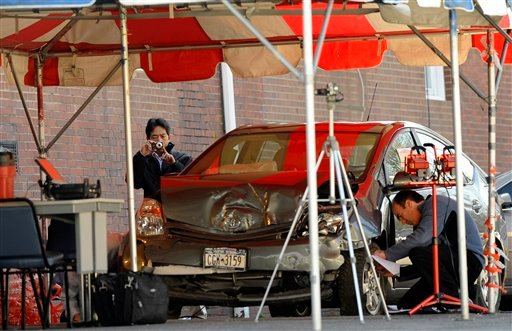 In this March 17, 2010 file photo, representatives of Toyota and the National Highway Traffic Safety Administration examine a crashed Toyota Prius in Harrison, N.Y.