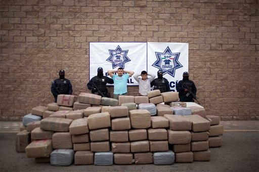 Federal police officers stand next to suspects Jesus Garcia, center left, and Juan Medina and packages of marijuana allegedly seized from them. (AP Photo/Guillermo Arias)