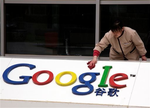 A worker cleans the sign in front of Google China headquarters in Beijing, Monday, March 22, 2010.