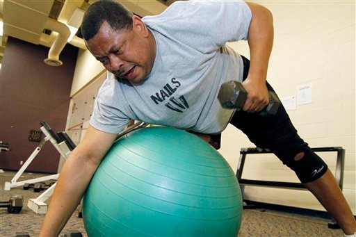 In this photo taken March 10, 2010, Sen. Eric Powell, D-Corinth, grunts as he lifts weights while trying to balance on a exercise ball during a predawn workout at Millsaps College. (AP Photo/Rogelio V. Solis)