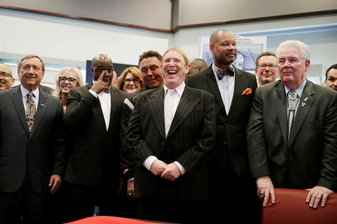 Oakland Raiders owner Mark Davis, center, laughs as he attends a bill signing ceremony with Nevada Governor Brian Sandoval, Monday, Oct. 17, 2016, in Las Vegas. Sandoval signed the bill into law that clears the way for a Las Vegas stadium that could be ho