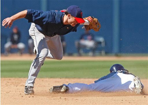 Cleveland Indians shortstop Jason Donald, left, dances over San Diego Padres' Everth Cabrera after making a sweeping tag to catch Cabrera trying to steal in the fourth inning of a spring training baseball game Sunday, March 14, 2010, in Peoria, Ariz. AP