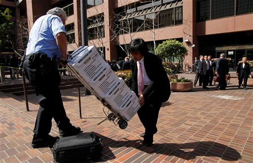 A security guard who declined to give his name helps Lam Tran, right, carry boxes containing documents on Toyota cases outside the federal courthouse in San Diego, Calif., Thursday, March 25, 2010. (AP)
